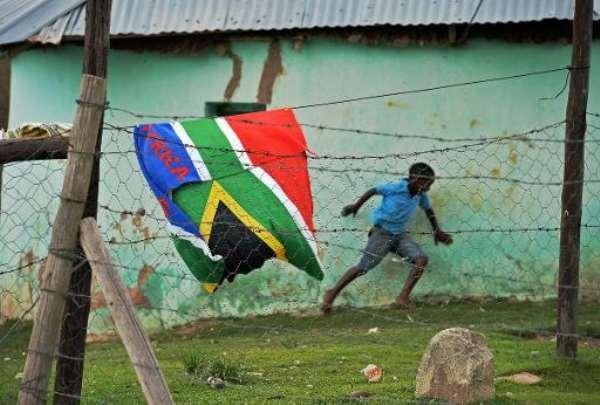 A boy runs past a South African flag near the former home of the late former South African president Nelson Mandela in Qunu on December 9, 2013.  By Carl de Souza (AFP)
