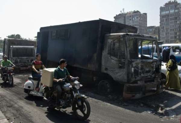 Egyptians ride past by a burnt-out police vehicle which was set on fire by Muslim Brotherhood supporters during clashes in Cairo, on October 7, 2013.  By Khaled Desouki (AFP)