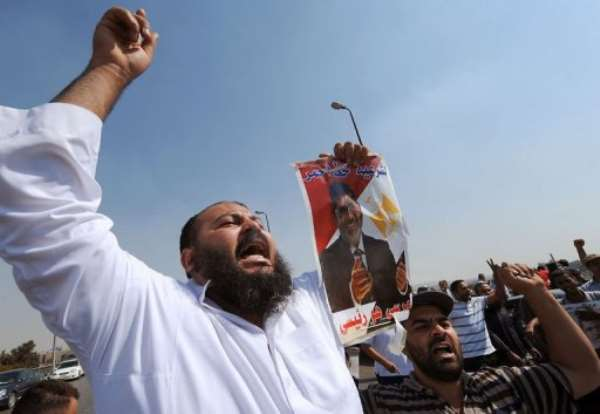 Egyptian supporters of the deposed president Mohamed Morsi carry posters on August 2, 2013.  By Fayez Nureldine (AFP)