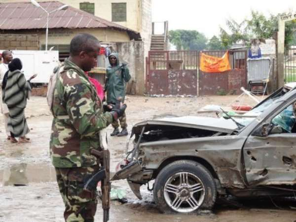 A soldier stands near a badly-damaged car at the scene of an explosion in Kano, northern nigeria on July 30, 2013.  By Aminu Abubakar (AFP/File)