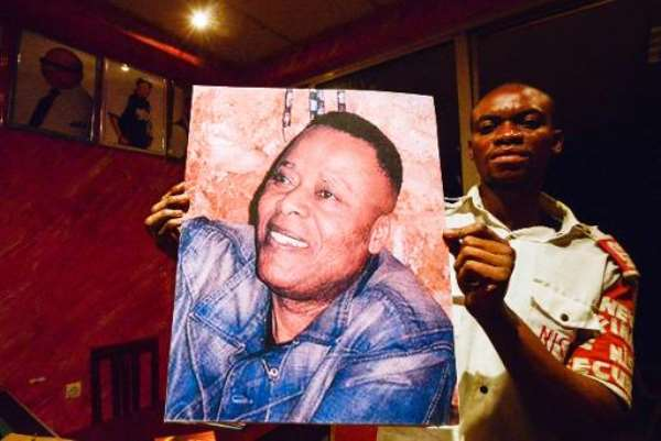 A man holds a picture of late Congolese singer King Kester Emeneya in the bar