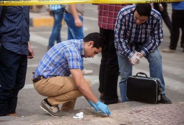Egyptian forensics inspect the site following a  bomb attack targeting a security checkpoint in central Cairo on April 15, 2014.  By Mahmoud Khaled (AFP)