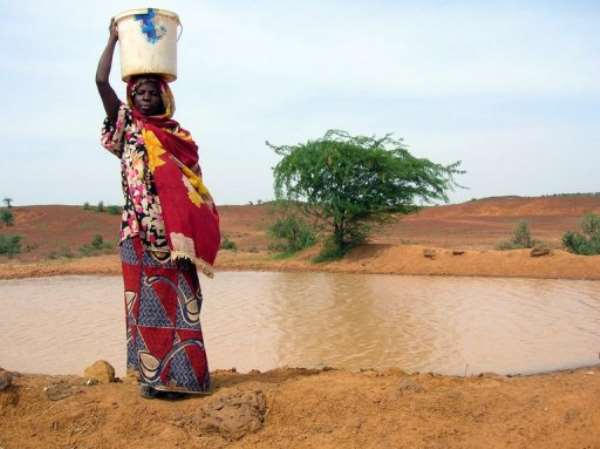 A woman continues to get water from a pool infected with cholera in Niger in 2005.  By Natasha Burley (AFP/File)