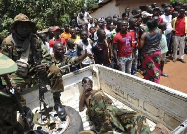 People watch Seleka rebels after they arrested men (in truck) suspected of looting in Bangui on March 26, 2013.  By Sia Kambou (AFP/File)