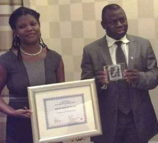 Doris Dzeha, Manager Operations and Alhassan Andani, CEO Stanbic Bank displaying the award plaque and certificate