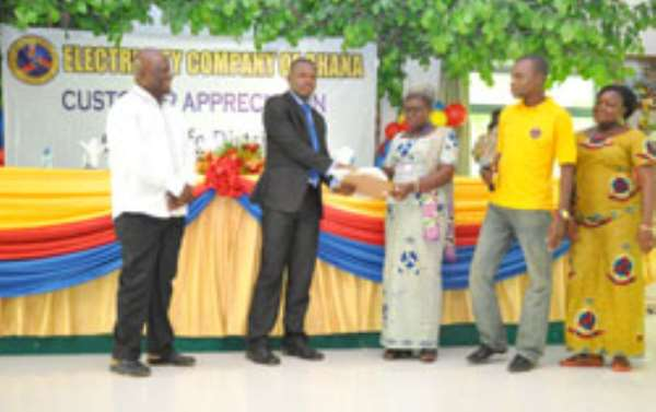Dr. Felix Anyah, looking as the Resident Doctor, Dr. Maxwell Onassis-Fiadjoe recieves the award for the Holi Trinity Spa from Mrs. Christine Hadzi