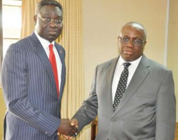Dr Wampah in a handshake with Philip Oduoza