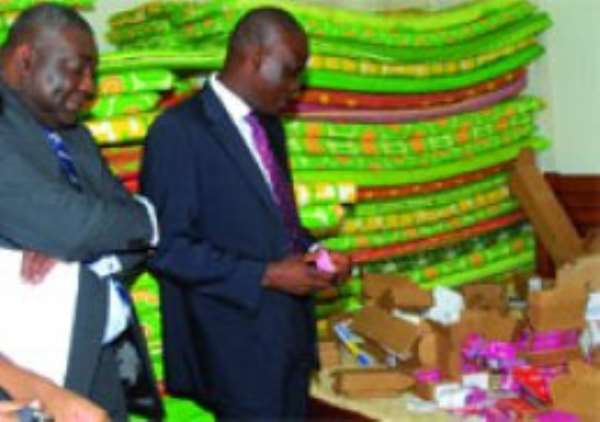 Mr Haruna Iddrissu (right), Communications Minister and Mr Paarock Van Percy, Director General of the National Communication Authority, inspecting some of the seized illegal Sim cards.