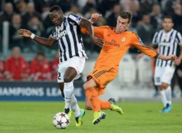Kwadwo Asamoah of Juventus (L) and Gareth Bale of Real Madrid compete for the ball during the UEFA Champions League Group B match