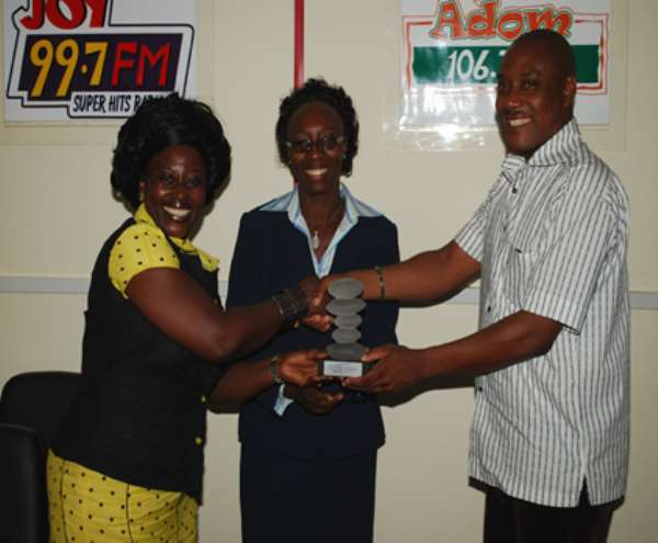Akumaa Mama Zimbi(left) presenting her award to Mrs Jane Gyekye,(middle) Head of HR and Corporate Resource and Mr Klaus Vonbackustein General Manager Asempa and Adom FM
