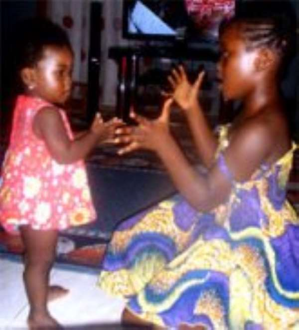 A one-year-old baby learning from her elder sister.