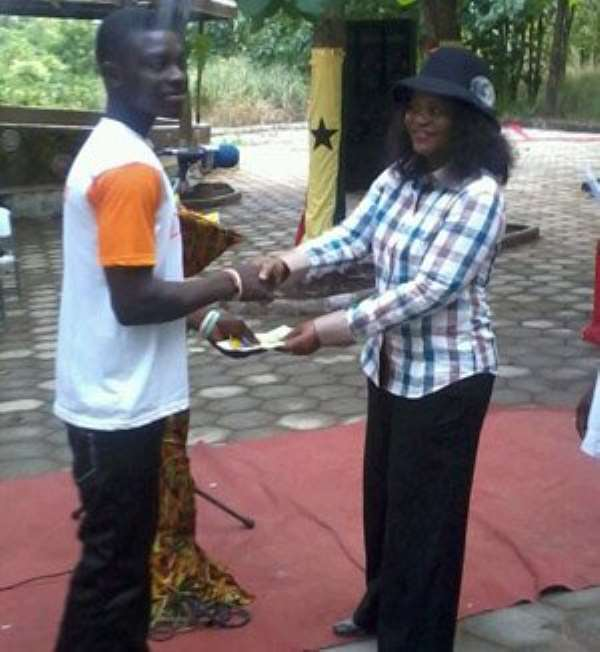 Regional Minister Helen Adwoa Ntoso presenting a prize to one of the bikers