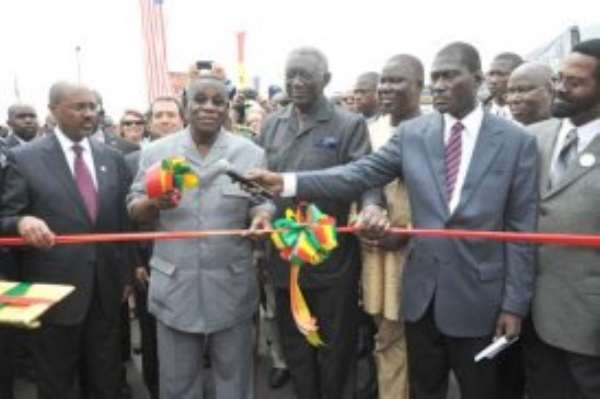 President Atta Mills (2nd left) being assisted by former President  John Kufuor (3rd left) to cut the tape to inaugurate the road