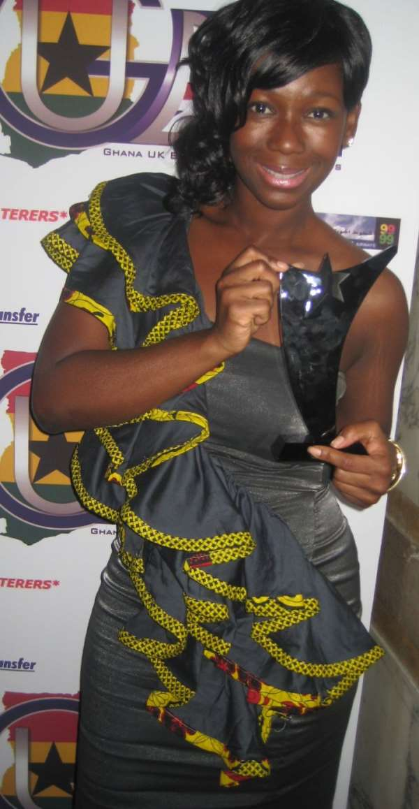 Presenter-Actress Ama K. Abebrese holding GUBA Award