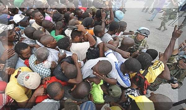 Haitians tear-gased as they scramble for food. Haitians: reduced to animals? Photo courtesy