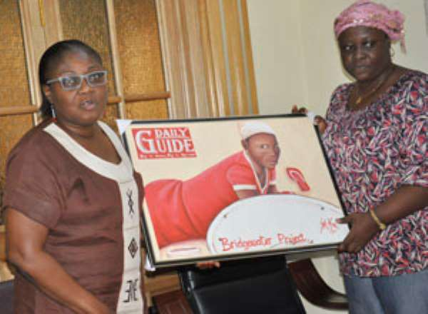 Mrs. Gina Blay receiving the painting from a representation of Kunata Voluntary Organisation