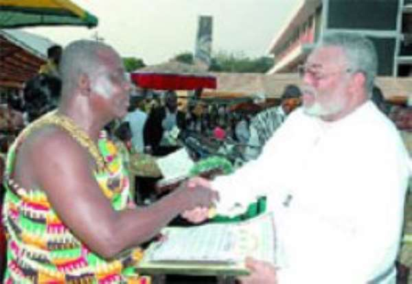 Pemanpam Yaw Kagbrese, Yejihene and Vice-President of the Brong Ahafo Regional House of Chiefs, presenting a plaque to former President Rawlings.