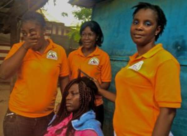 Young women learn how to braid hair at the Peculiar Touch Beauty Institute