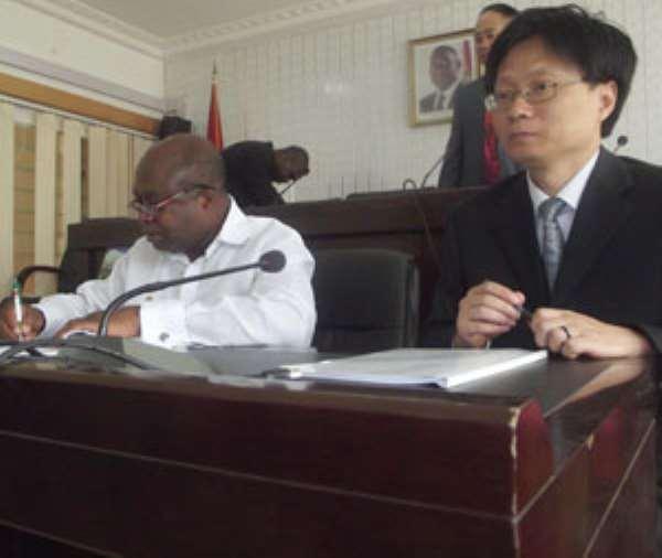 Hon Humado (L) and Zhou Jun, Group leader signing the MOU