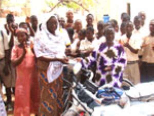 Headmistress of Zorkor SHS, Madam Abubakari Memuna receiving the papers of the motorbikes from Mr. Christopher Azaare, Zorkor SHS PTA chairman