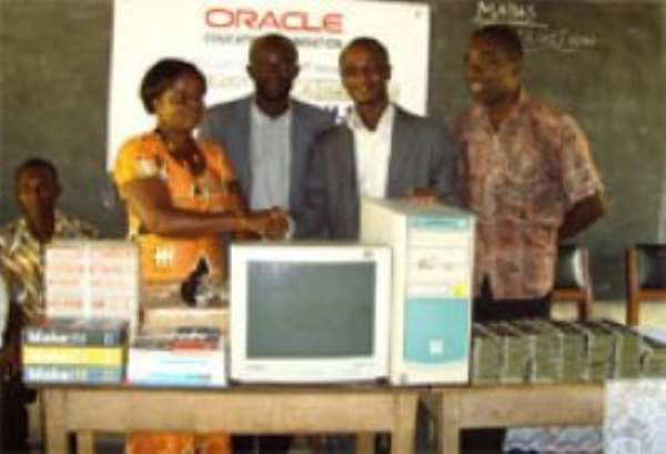 Technology Pre-sales Consultant of OEF, Mr Harry K. Tetteh (second right), presenting the items to the Headmistress of the School, Mrs Margaret Antwi left.