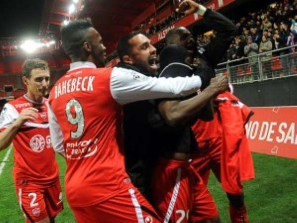 Waris is mobbed by his team-mates after scoring the winner
