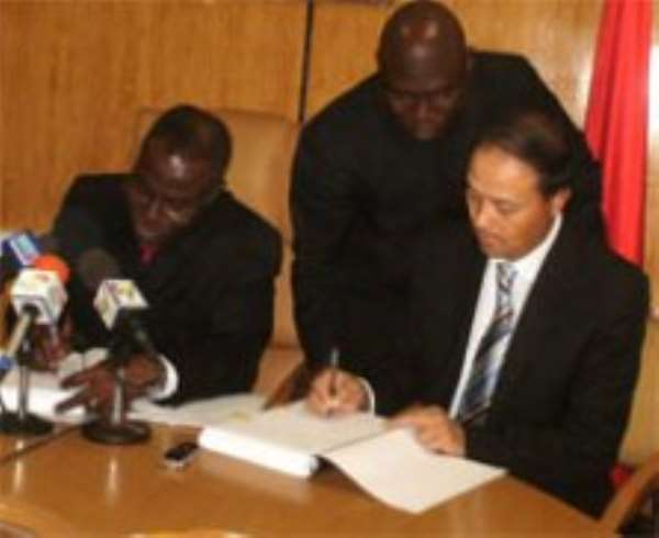 Dr Joe Oteng-Adjei (left), appending his signature to the agreement while Mr Yu Guohui (right) initials for his Group. Looking on is a Deputy Energy Minister, Alhaji Inusah Fuseini.