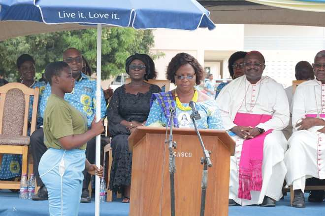 Madam Abla Avevor, Headmistress of St. Catherine Senior High School in the Keta-Akatsi Diocese addressing the audience. Seated Behind are Bishop Anthony Adanuty Founder of School and Bishop Gabriel Kumordji of Keta-Akatsi October 19, 2019. Photo by Damian Avevor