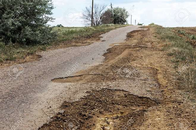 162020113934-swnaqdcp53-106072669-damaged-road-cracked-asphalt-sword-with-potholes-and-spots-ukraine-very-bad-asphalt-road-with-large-