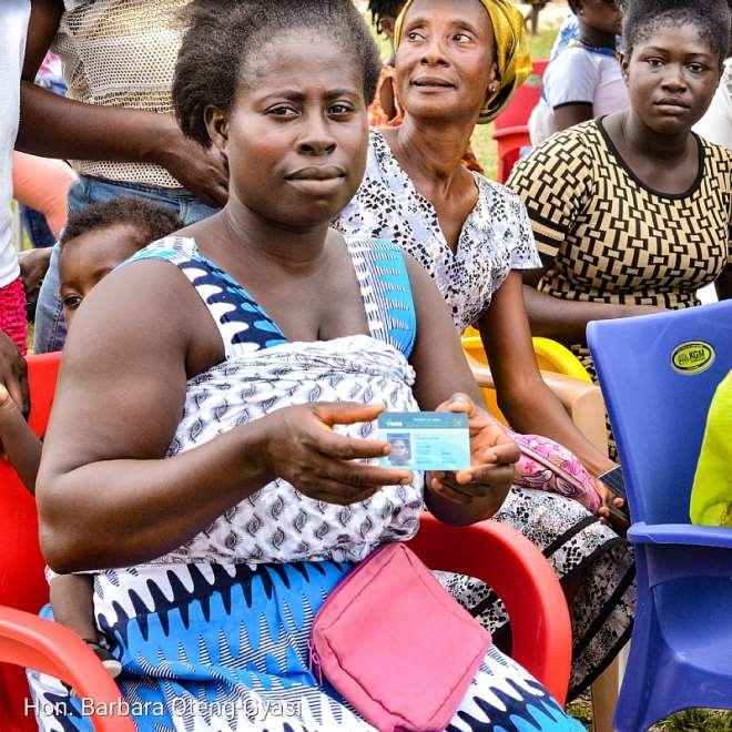 A widow displaying her renewed health insurance card