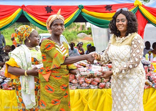 Tourism minister handing over a piece of cloth to a widow whiles a woman organiser looks on