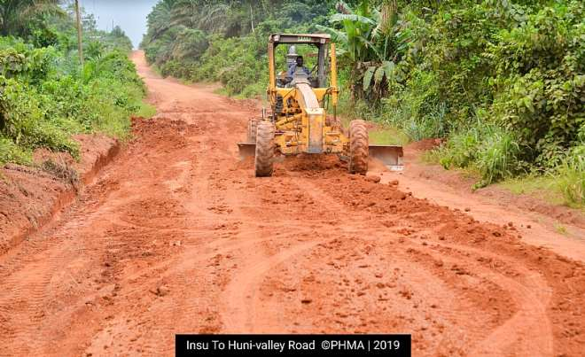 A grader busily working on the road