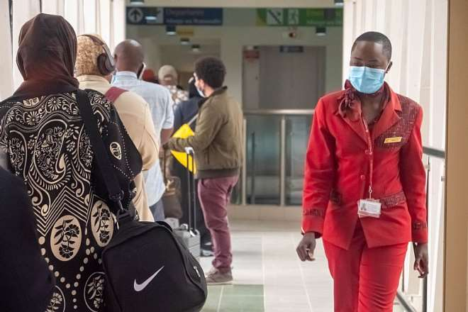 812020124342-1i841p5bbv-passengers-queue-to-board-kenya-airways-flight-100-to-london-at-jomo-kenyatta-international-airport-