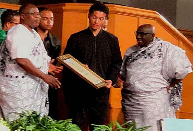 Deputy Minister of Foreign Affairs, supported by HE Papa Owusu Ankomah, presenting the posthumous award to the son of Dr Teye-Botchway.