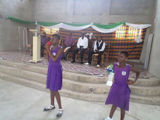 A FEMALE PUPIL RECITING A POEM ON WHAT SHE HOPE TO ACHIEVE AND HOW SHE CAN SUPPORT THE DEVELOPMENT OF HER COMMUNITY