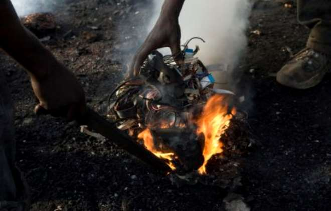 Burning off the plastic insulation from computer wiring to get the copper at a dump in Accra, Ghana