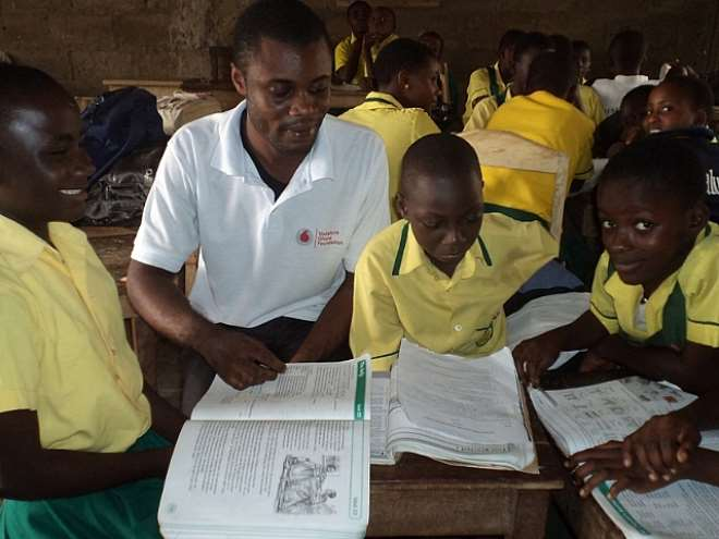 COORDINATOR ASSISTING PUPILS WITH BASIC READING FUNDAMENTALS IN A A GROUP ACTIVITY