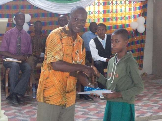 DR. SAMUEL ACQUAH PRESENTING AWARD TO ONE OF THE PUPILS