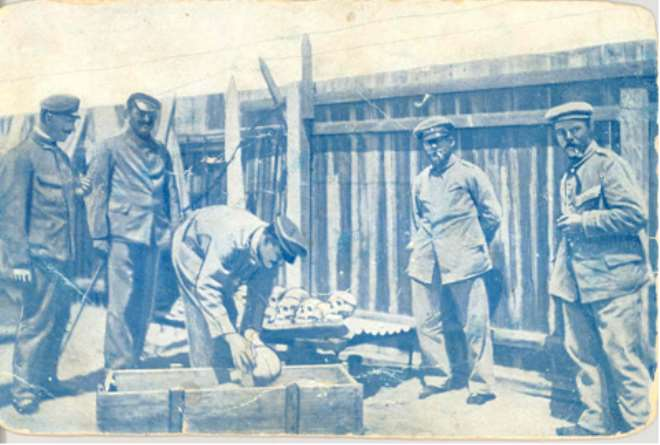 German soldiers loading human skulls and bones of massacred Hereros into a casket for shipping to German universities, especially, Berlin.