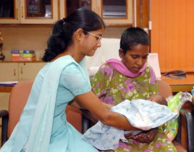 Saraswati being given her son for the first time since his birth.