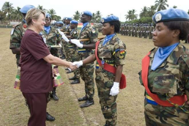 un envoy shakes hands with ghanaian medal recipient