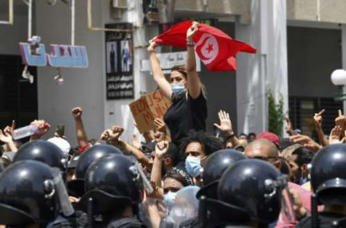 A Tunisian protester waves the national flag at an anti-government rally in front of parliament in Tunis on Sunday.  By FETHI BELAID (AFP)