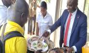 Isaac Owusu serving food to the journalists