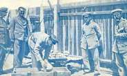German soldiers loading human skulls and bones of massacred Herero into a casket for shipping to German universities, especially, Berlin.