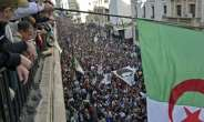 Algerians wave a national flag from a balcony as they watch anti-government demonstrators march in the capital Algiers on Friday.  By RYAD KRAMDI (AFP)