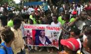 Demonstrators hold a poster portraying Liberian President George Weah as they gather outside the Liberian Mansion in Monrovia on June 7, 2019 during an anti-government march to protest inflation and corruption.  By CARIELLE DOE (AFP/File)