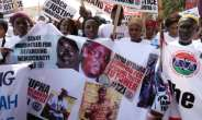 Wearing T-shirts that read #justicemustprevail, the protesters held photographs of people killed during Jammeh's rule.  By ROMAIN CHANSON (AFP)