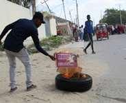 A man burns a poster of Somali President Mohamed Abdullahi Mohamed in Mogadishu in December 2020 amid a political impasse.  By STRINGER (AFP/File)