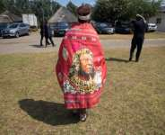 A mourner at last week's funeral wears a cloak bearing the image of the king.  By Phill Magakoe (POOL/AFP)