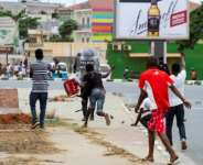 A protester throws a rock at a police officer during an anti-government demonstration in Luanda in October 2020: falling oil prices and the coronavirus have hit the country hard.  By Osvaldo Silva (AFP)